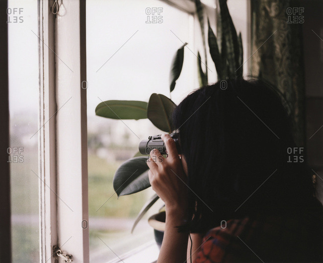 A woman looking out the window through binoculars