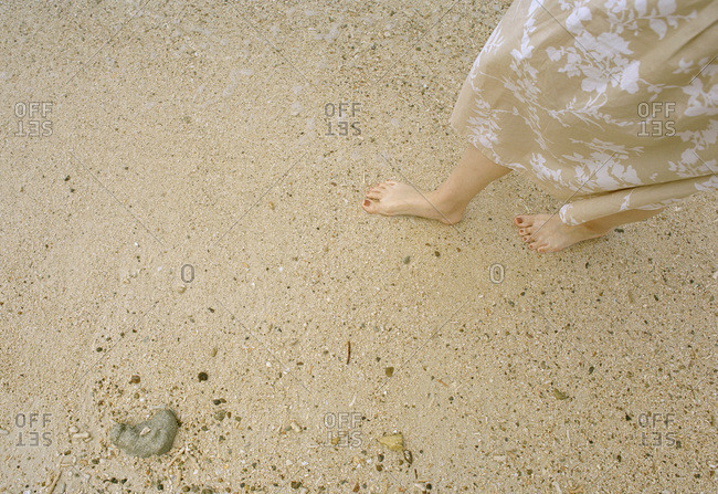 A woman's feet on a sandy beach