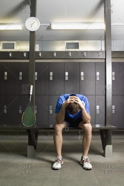 A man resting in a locker room