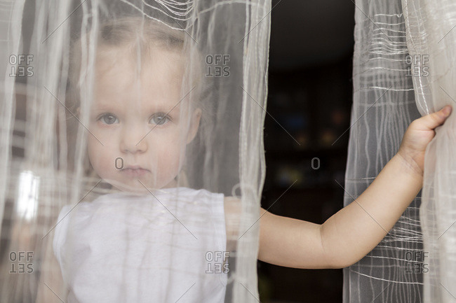 Girl staring behind translucent curtains