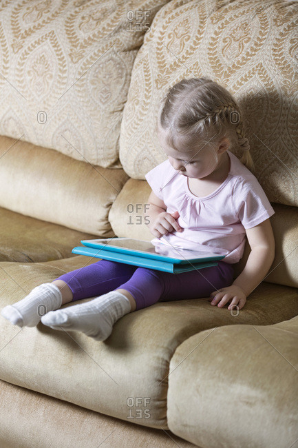 Little girl playing with a digital tablet on sofa