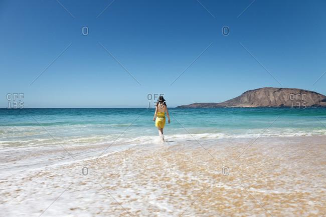 Woman walking through water on beach in La Graciosa, Canary Islands, Spain