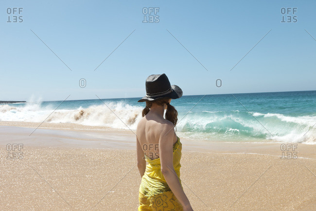 Woman on beach looking at waves