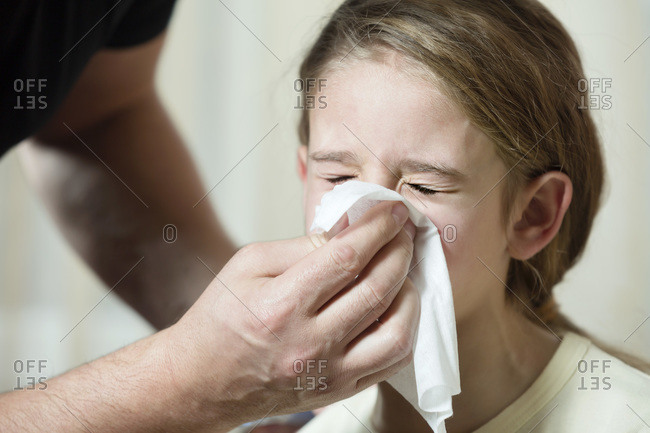 Father wiping daughter's nose with tissue