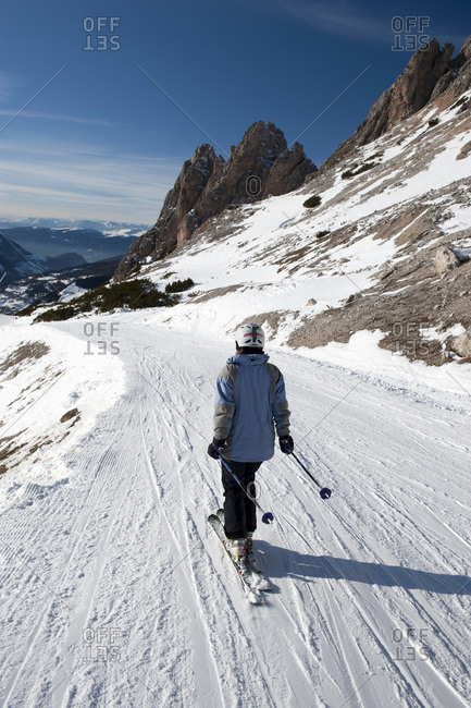 Skier with view of snow-capped mountains of The Dolomites, South Tyrol, Italy,