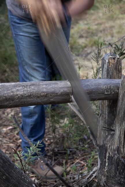 Man cutting log with saw