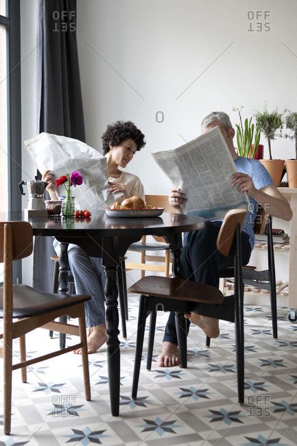 A hip mixed aged couple reading newspapers and having breakfast