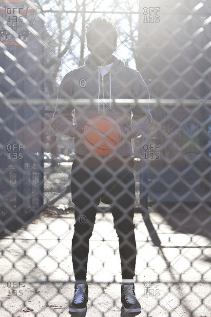 A hip young man holding a basketball and standing on an outdoor basketball court