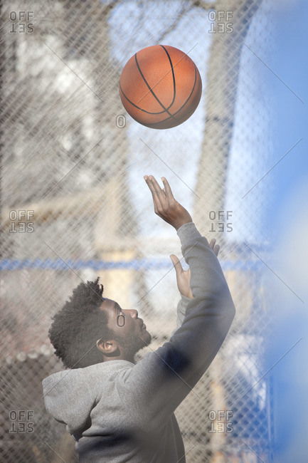 A hip young man playing basketball on a public outdoor court
