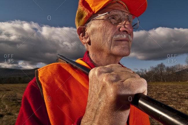 Older man bird hunting in a field in autumn