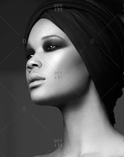 Head shot of dark-haired model in head wrap