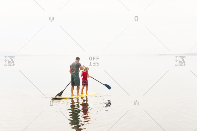 Caucasian father and daughter riding paddle board