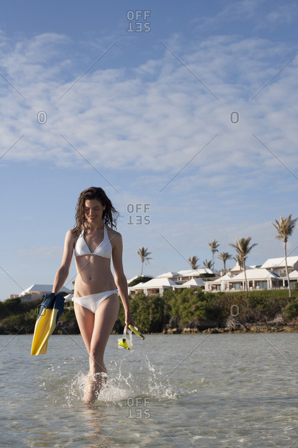 Woman with snorkel gear wades in shallow water