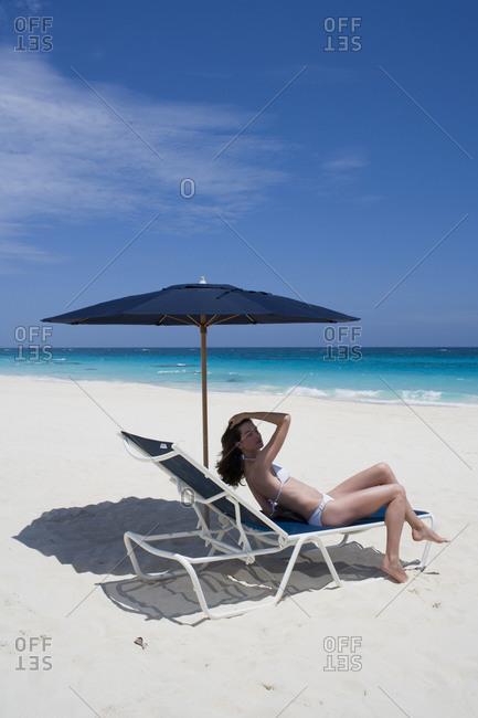 Woman in bikini on lounge chair under umbrella on beach