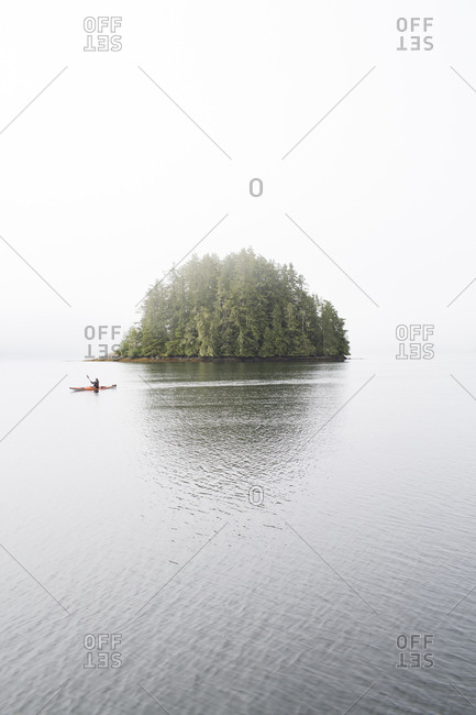 Woman kayaking near small pine tree covered island on a foggy day near the Clayoquot Wilderness Resort