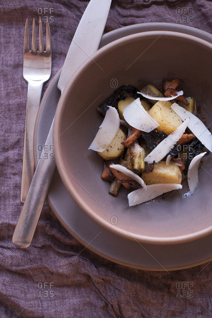 Overhead view of bowl of roasted potatoes with slices of cheese over linen tablecloth