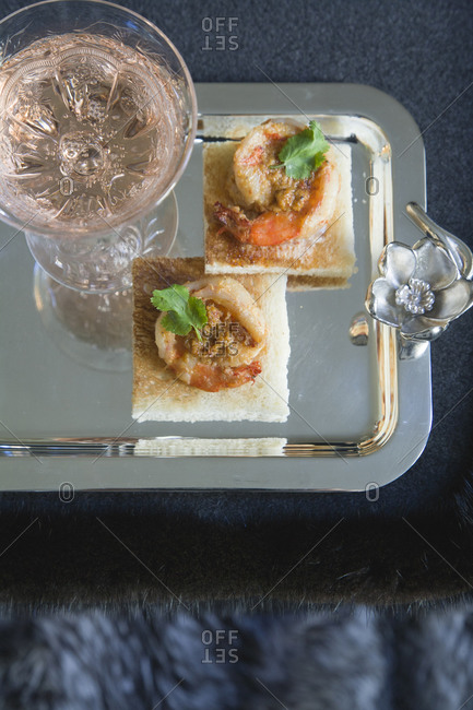 Tray with Malaysian spiced shrimp on crackers and glass of sparkling wine