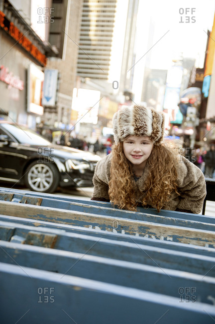 A young girl leaning on Police barricades in Times Square