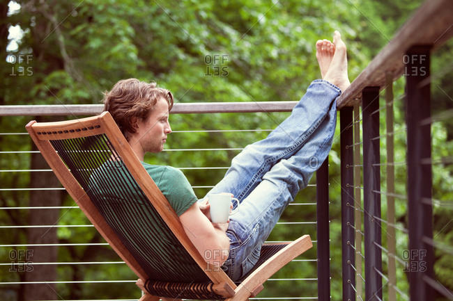 Young man sitting on terrace with legs on railing