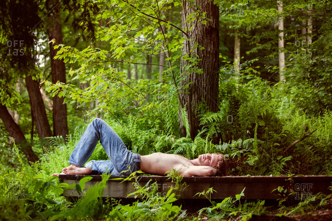 Barechested young man lying on the pier while daydreaming