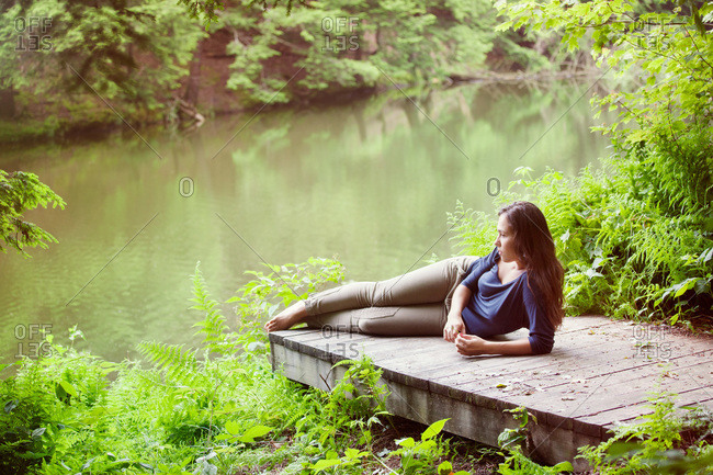 Young brunette girl lying on pier in the nature