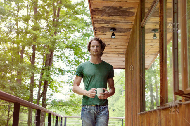 Low-angle view of young man walking on porch with white mug