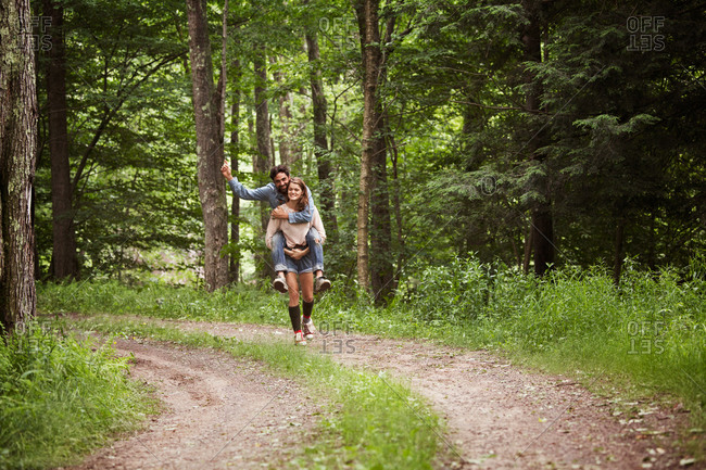 Young woman carrying her boyfriend on her back on dirt road