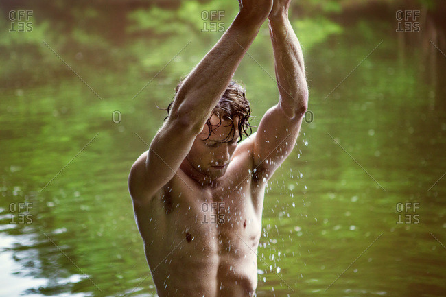 Barechested man splashes water on himself