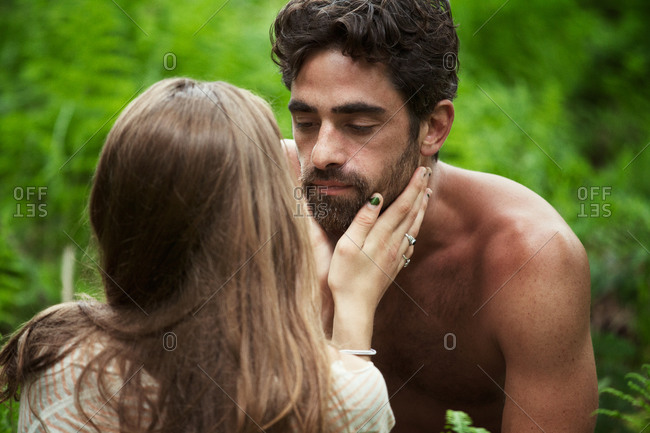 Young man bending over his girlfriend among green ferns