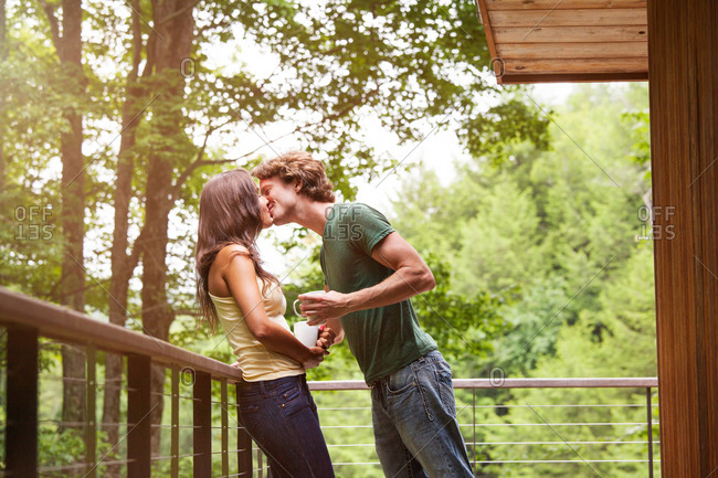 Young pair kissing on porch