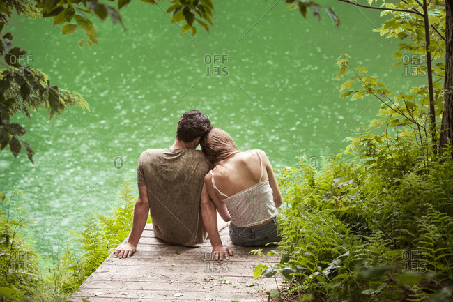 Young couple in love on pier by lake