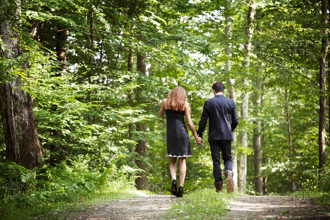 Rear view of young couple walking in forest