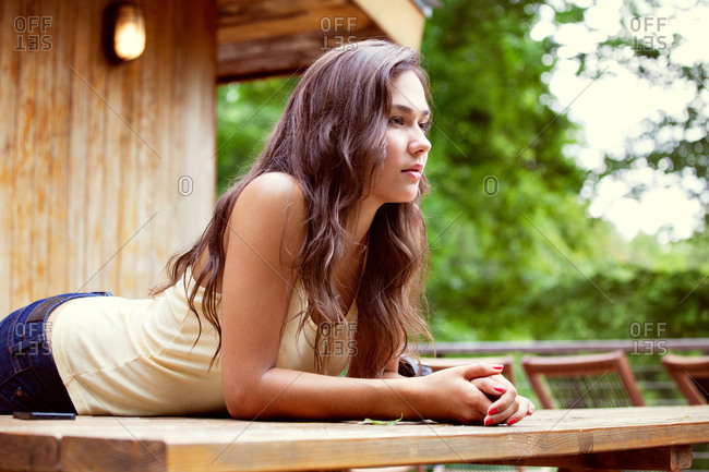 Portrait of young woman leaning on wooden table