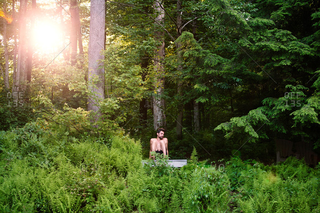 Young man sitting in woods