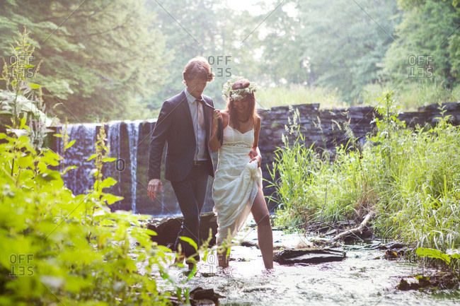 Bride and groom walking in creek