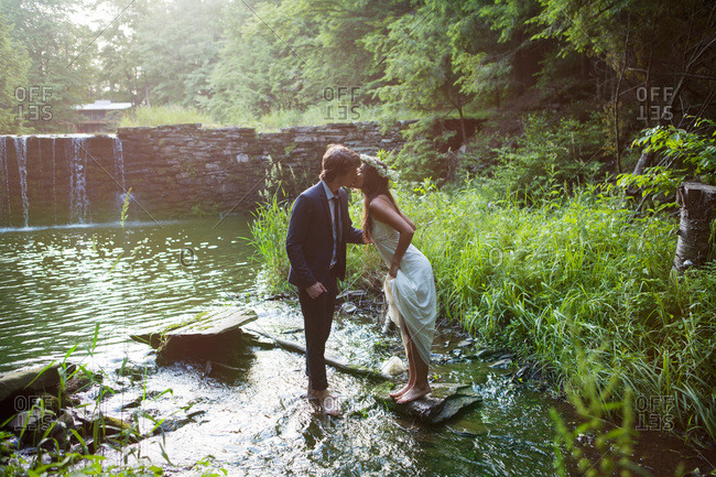 Young couple kissing in the forest stream
