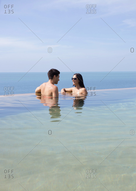 Couple conversing while standing in resort pool