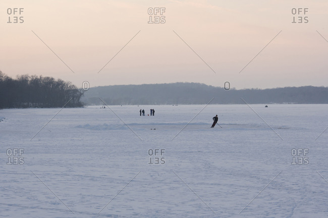 People on frozen ice of lake Monona, including a single ice hockey player