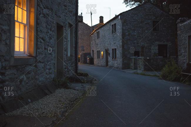 Illuminated window in stone house along village roadside at dusk