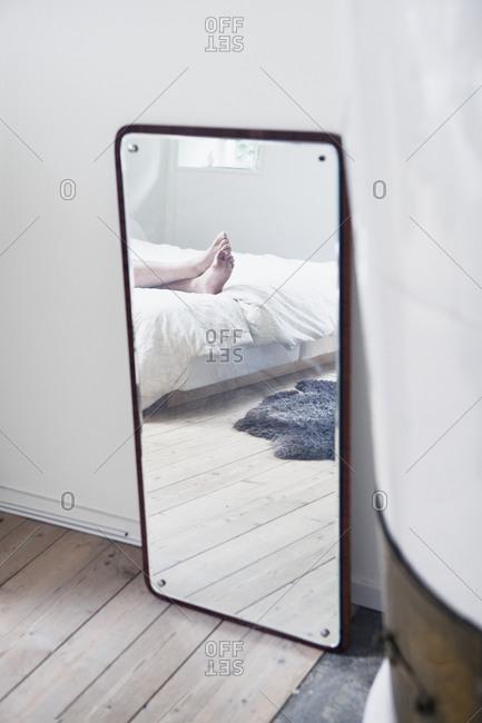 Human feet reflecting in bedroom mirror