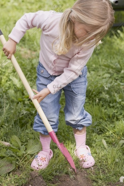 Little girl gardening with a spade