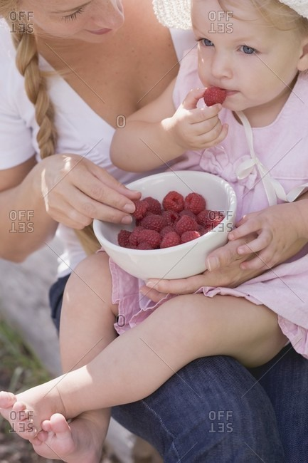 Mother and young daughter eating raspberries