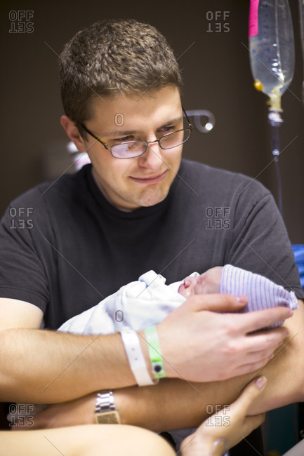 Father with newborn baby in delivery room