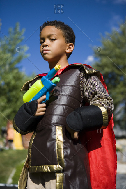 Boy posing in costume and water gun