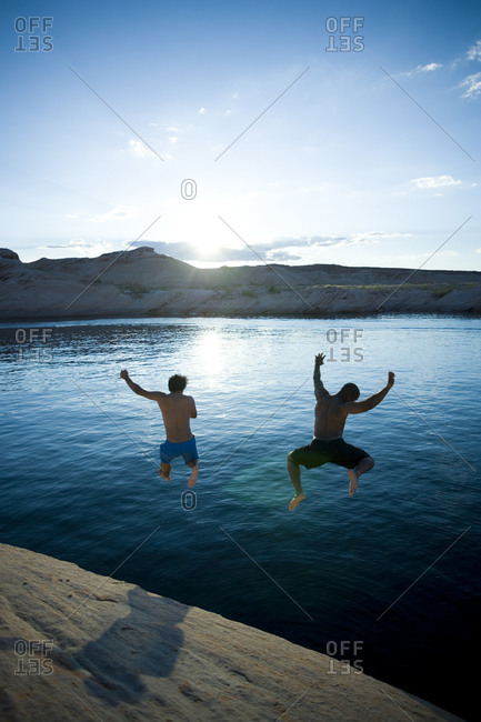 Two men diving into water at sunrise
