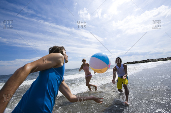 Three adults playing with a beach ball