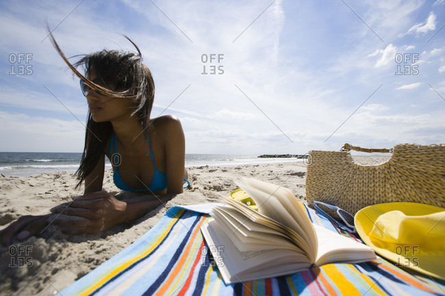 Woman lying on beach with book and beach bag