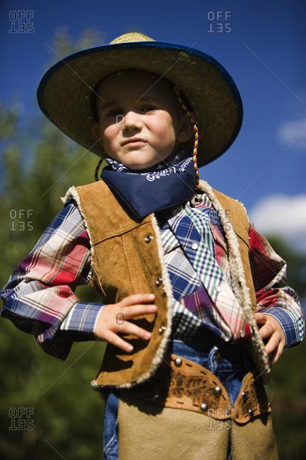 Boy in cowboy costume outside