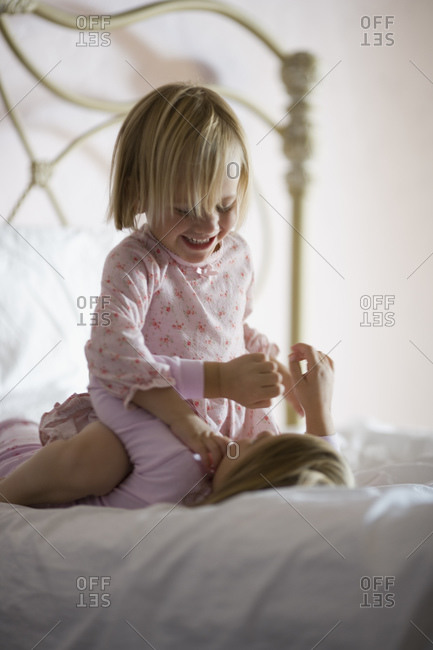 Two girls playing on bed