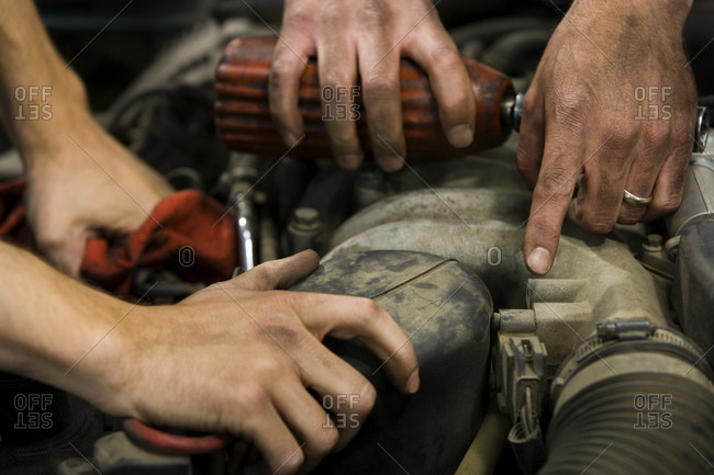 Closeup of four male hands fixing car